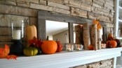rustic mantel styling with candles, faux pumpkins, branches and a mirror in a vintage stained frame