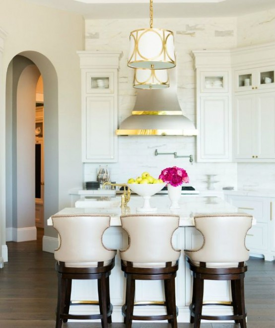 a small vintage glam kitchen in white, with elegant cabinetry, white stone countertops, vintage chairs and a shiny metal hood