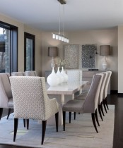 a sophsticated neutral dining room with a chic table with a stone tabletop, neutrla upholstered chairs, lovely lamps and some art