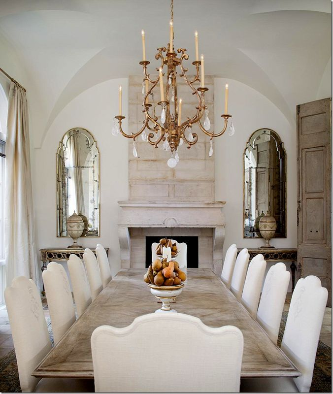 a neutral dining room with a long whitewashed table and neutral chairs, a fireplace, a crystal chandelier and vintage mirrors