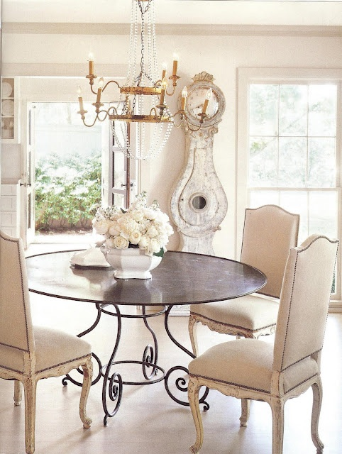 a shabby chic neutral dining room with a metal table, vintage upholstered chairs, a refined crystal chandelier and a whitewashed shabby chic clock
