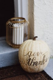 a pillar candle in a candle holder and a neutral pumpkin with letters compsoe a cool decoration for outdoors