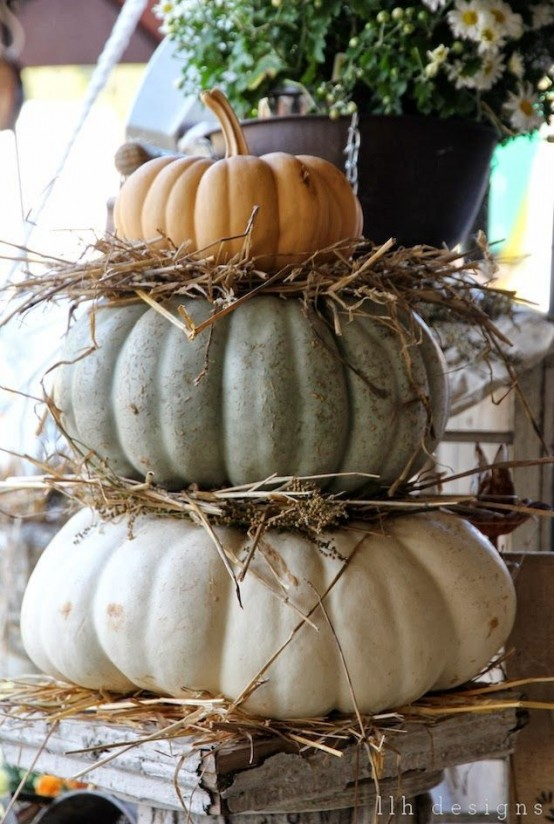 a stack of heirloom pumpkins with hay is a gorgeous rustic decoration for indoors or outdoors