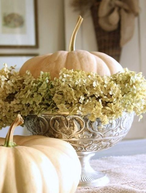 a vintage bowl with dried hydrangeas and a single white pumpkin is a stylish vintage-inspired centerpiece or decoration