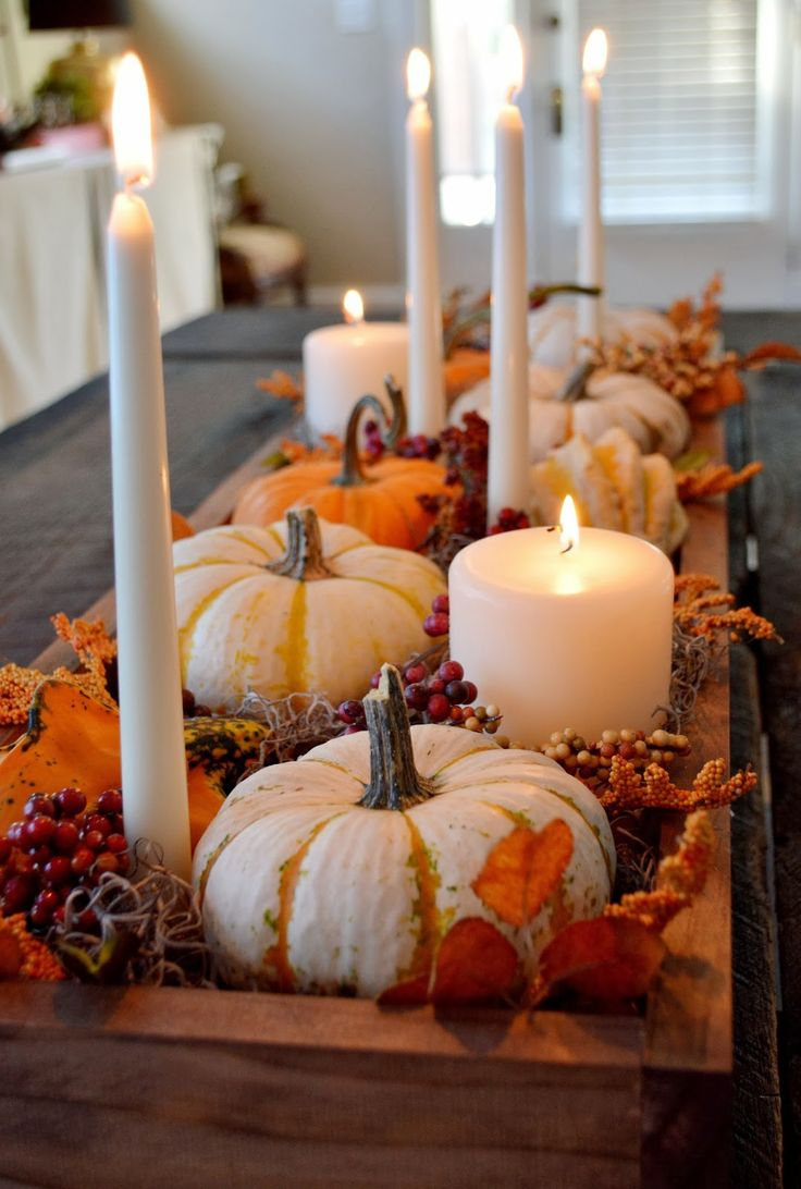 a wooden box with hay, berries, pumpkins, gourds and tall and pillar candles is a stylish rustic centerpiece for Thanksgiving