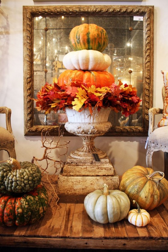a vintage urn with lush fall leaves and a stack of natural pumpkin will give a vintage and rustic feel to the space