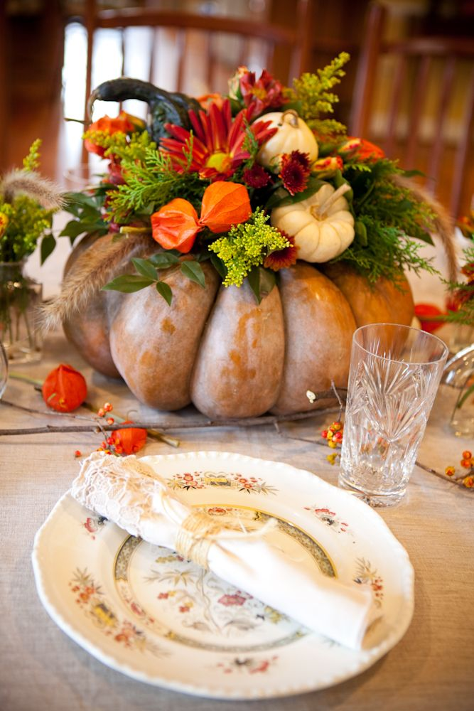 an oversized heirloom pumpkin with greenery, bright blooms and mini white pumpkins as a bold Thanksgiving centerpiece