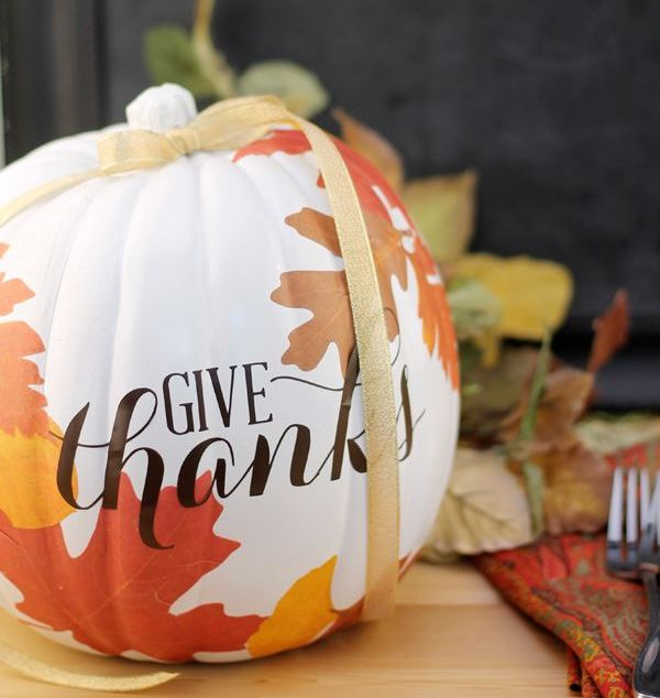 a beautiful white pumpkin with decoupaged fall leaves on it and a yellow ribbon is a chic decoration for Thanksgiving