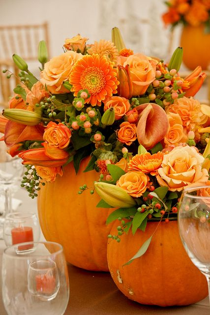 bright orange pumpkins with bright orange blooms, greenery and berries for Thanksgiving centerpieces or decorations