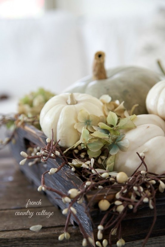 a wooden box with dried hydrangeas, pumpkins and branches with berries is a chic neutral rustic centerpiece for Thanksgiving