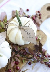 a cutting board with cherries, greenery and white pumpkins with tags for a Thanksgiving centerpiece
