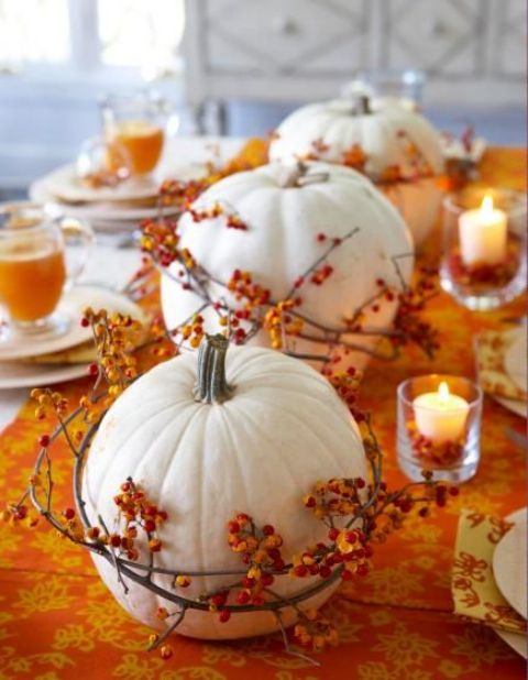 white pumpkins wrapped with berry branches and with candles are a nice Thanksgiving centerpiece or decoration