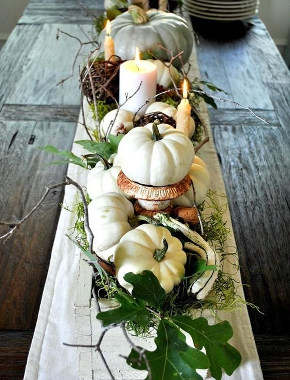 a Thanksgiving table runner of pumpkins on stands, greenery, antlers, twigs and candles