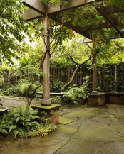 a townhouse garden with a wooden fence, planted greenery and a wooden cabana all covered with living greenery