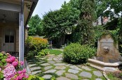 a large townhouse garden with stones, grass, a fountain, planted greenery and bright blooms