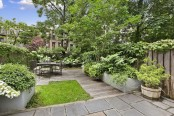 a small townhouse garden with a lawn, a wooden deck, potted greenery and blooms and a small wooden dining set