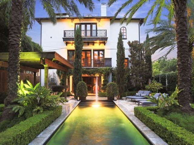 a large townhouse garden with a pool with a waterfall, planted trees, palms and greenery plus contemporary furniture