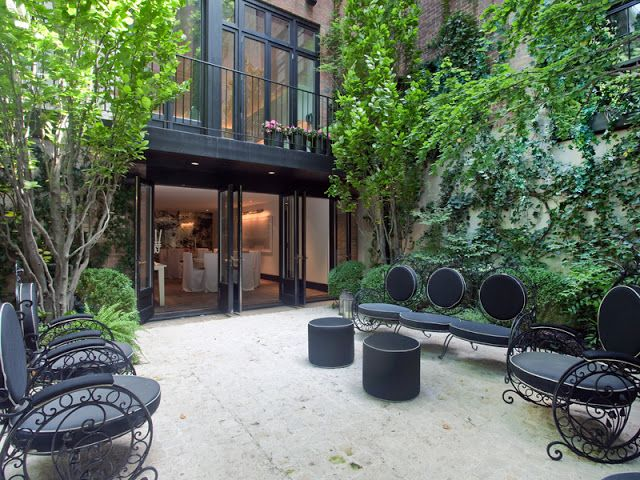 a contemporary townhouse terrace with a stone floor, a living wall and trees plsu catchy black furniture
