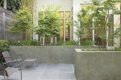 a small townhouse garden with stone tiles, concrete flower boxes, minimalist furniture and greenery and trees growing