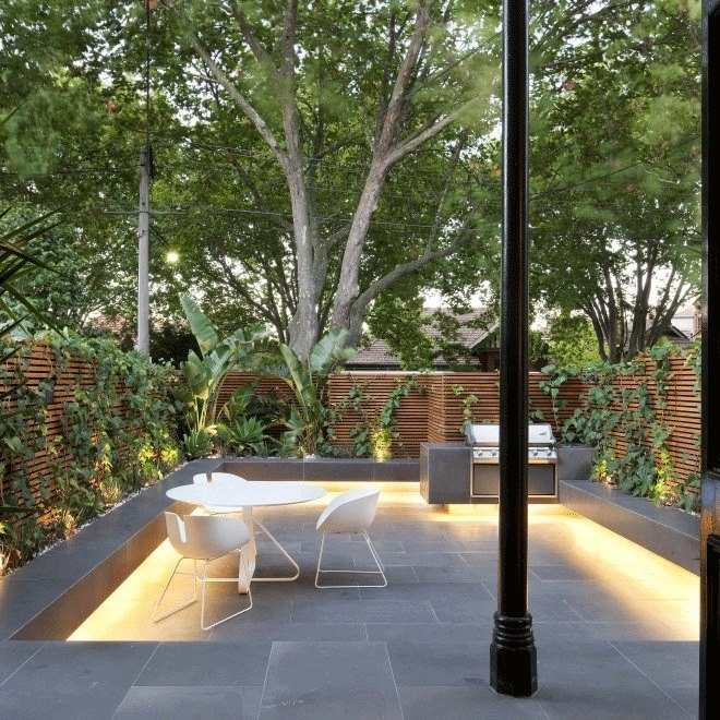 a minimalist townhouse garden done with stone tiles, additional lights, benches and living walls