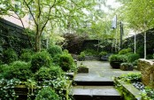 a lush townhouse garden with a stone deck and steps, living walls and potted greenery plus a basketball ring