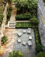 a contemporary townhouse garden with a wooden deck and concrete tiles, contemporary furniture and planted greenery
