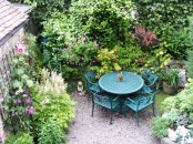 a small rustic townhouse garden with lush greenery and blooms plus a blue dining set