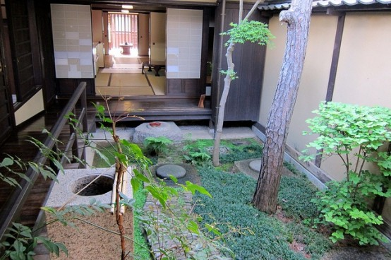 a zen townhoue garden with greenery, a tree, stones and rocks inspired by traditional Japanese esthetics