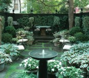 a welcoming shady garden with living walls and potted greenery plus some garden furniture and a small fountain