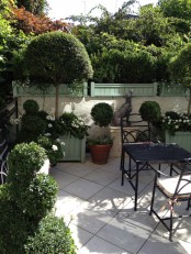 a small townhouse garden with potted greenery and a tree, blooms in wooden crates and vintage garden furniture