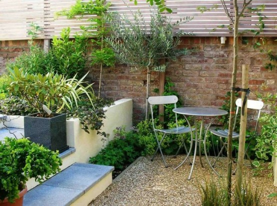 a cozy small garden space with built-in and metal furniture and some greenery around