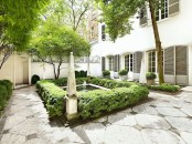 an elegant garden space with large tiles, a fountain with planted greenery lining up the fountain and the whole space