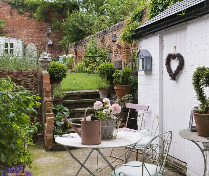 a cozy rustic meets vintage garden space with vintage garden furniture, a cool lawn and potted greenery