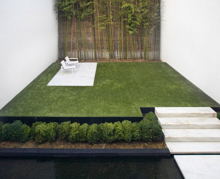 a minimalist garden space with stone steps, a manicured lawn, planted greenery and bamboo and minimalist furniture