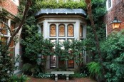a small townhouse garden done with brick and planted greenery of various kinds