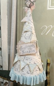 a large note paper cone wrapped in paper buntings, beads, signs and a pink fabric flower on top