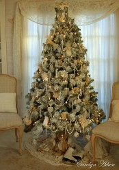 a beautiful white Christmas tree with lights, beads and ornaments in white and silver and some vintage toys under the tree