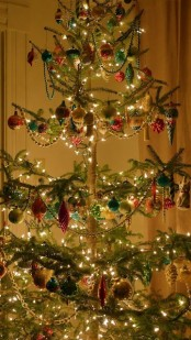 a Christmas tree with lights, bead garlands and colorful Christmas ornaments in red, green and pink