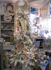 a whimsy white Christmas tree with lights, Christmas ornaments, white evergreens and signs