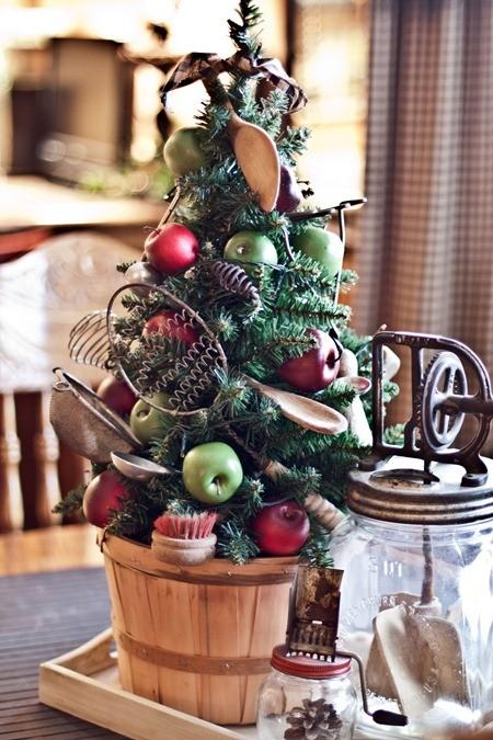 un mini sapin de Noël amusant dans un panier en bois, avec des pommes, des cuillères en bois, des accessoires de cuisine en métal