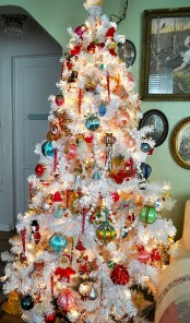 a white Christmas tree done with lights and bright vintage Christmas ornaments looks bold and very enchanting