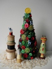 a bright green and red Christmas tree composed of buttons, with spools around for vintage table styling