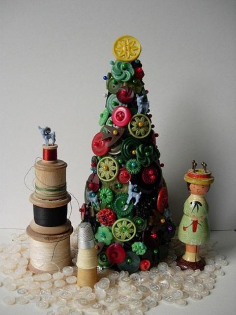 un arbre de Noël vert et rouge vif composé de boutons, avec des bobines autour pour un style de table vintage
