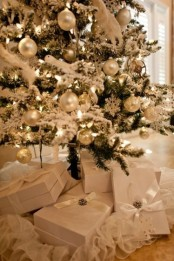 a flocked Christmas tree with silver and mother of pearl ornaments and lights looks really charming and chic
