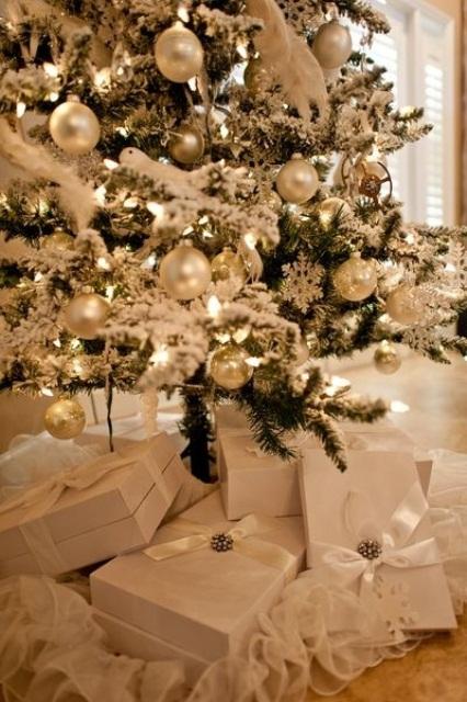 un arbre de Noël floqué avec des ornements et des lumières en argent et en nacre a l'air vraiment charmant et chic