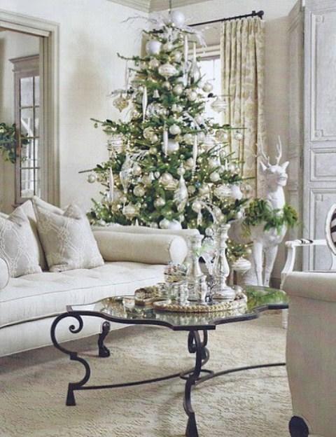 un arbre de Noël avec des décorations de Noël transparentes et argentées, des décorations habituelles et surdimensionnées ainsi que des lumières a l'air très charmant
