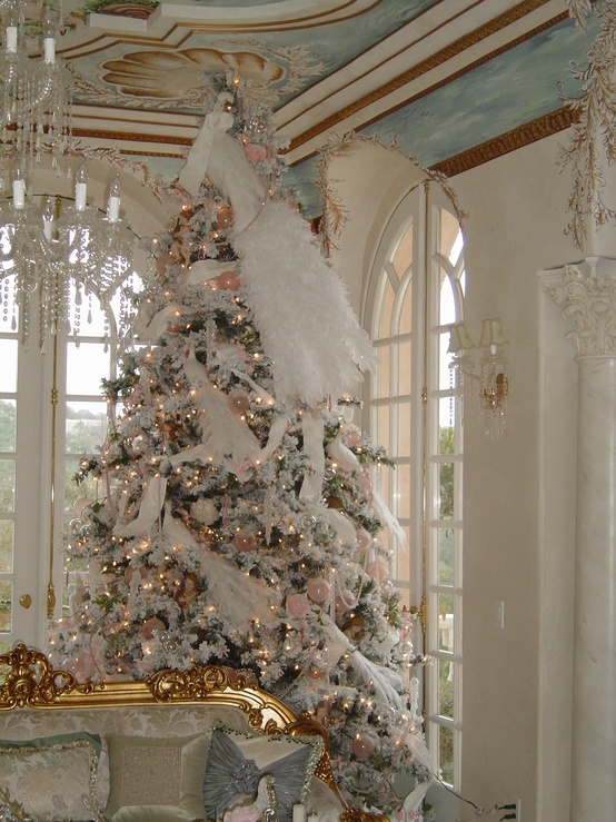 a flocked Christmas tree with pink ornaments, lights, white feathers and faux birds looks refined and very catchy