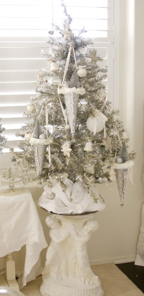 a silver Christmas tree done with white and silver ornaments, silver cones with decorations looks very vintage and serene