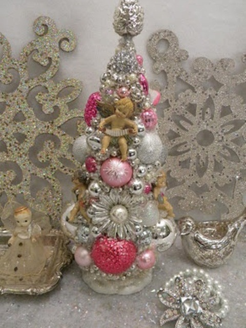 a vintage tabletop Christmas tree composed of vintage ornaments in silver and bright colors plus brooches