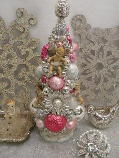 un arbre de Noël de table vintage composé d'ornements vintage en argent et couleurs vives ainsi que des broches